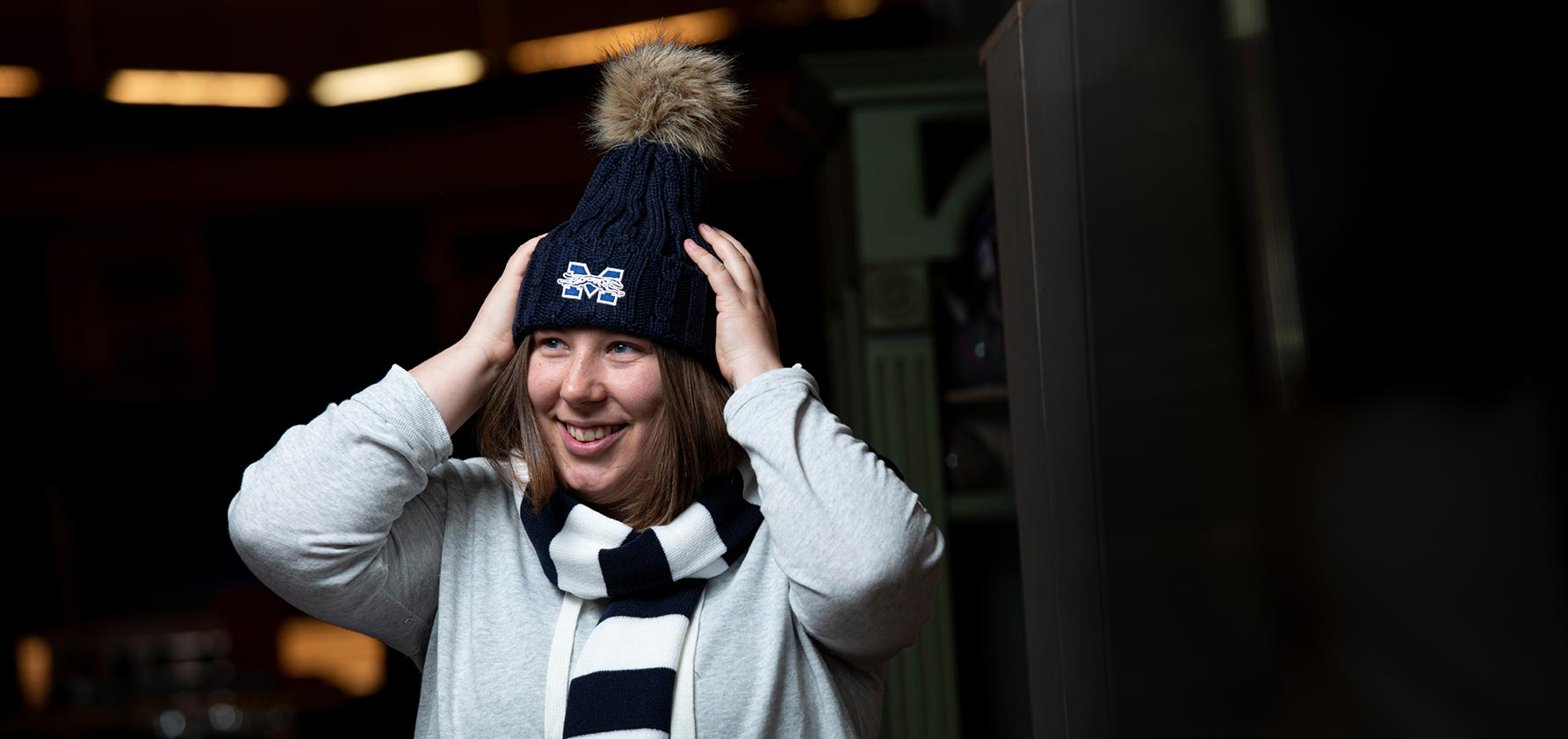 Claire Boucher tries on a hat in the Moravian College Book Shop.