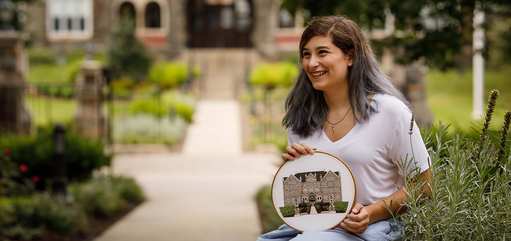 Gabriela Landi '20 stands in front of Comenius Hall with her embroidery of the building.