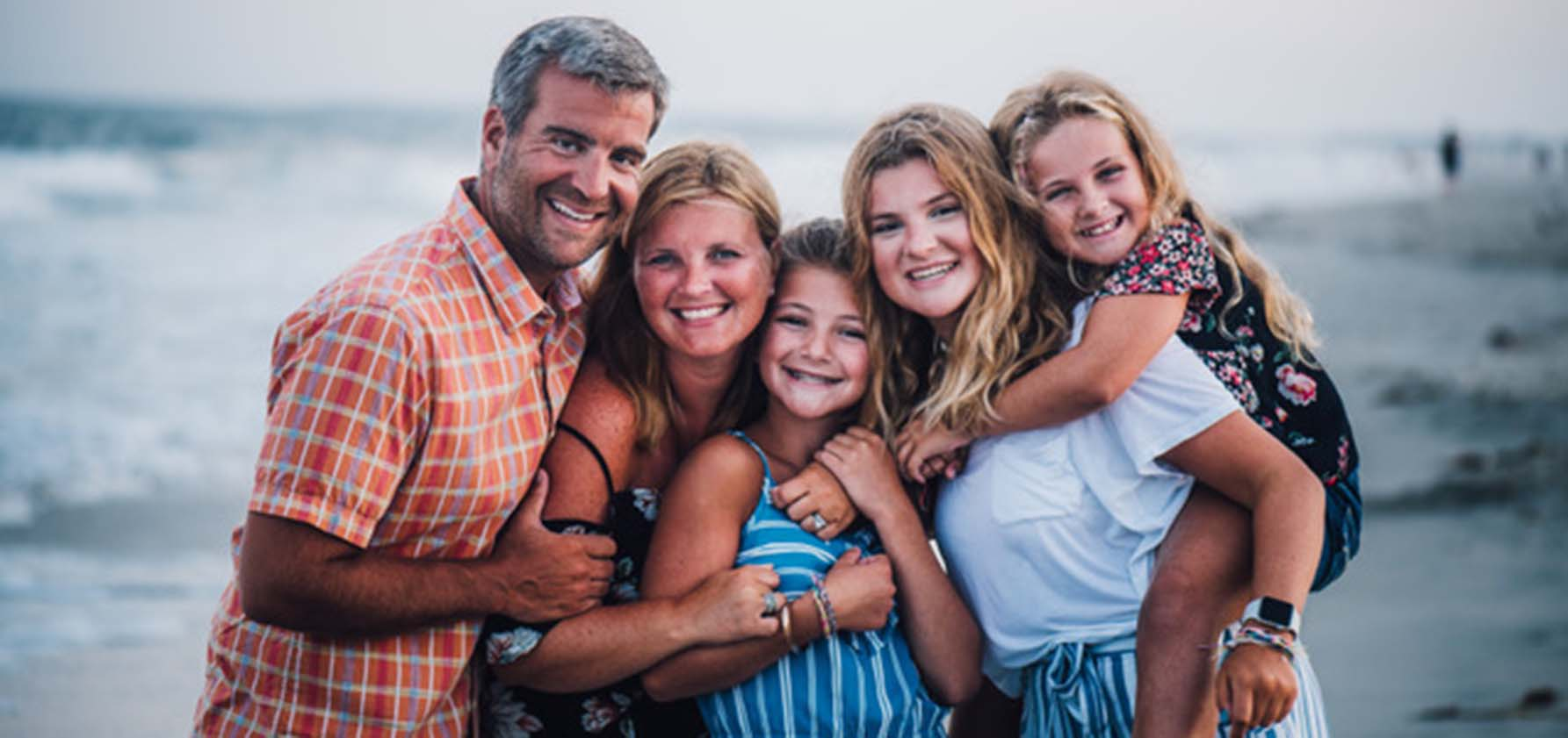 James Coupe '98 and family smile for a family portrait at the beach in the summer of 2019.