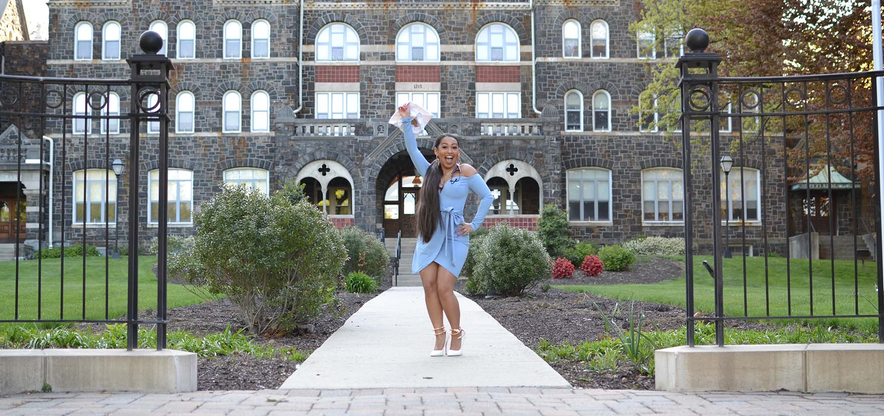 Janiya Punzalan '20 celebrates her BS in nursing in front of Comenius Hall.