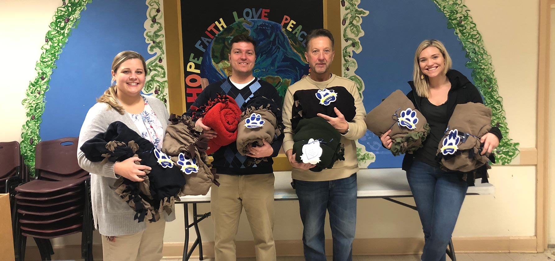 Paula Young, Dan Miller, Tom Pheiffer, and Grace Young at the Northeast Community Center receive blankets made during Moravian College's 2019 Heritage Day.