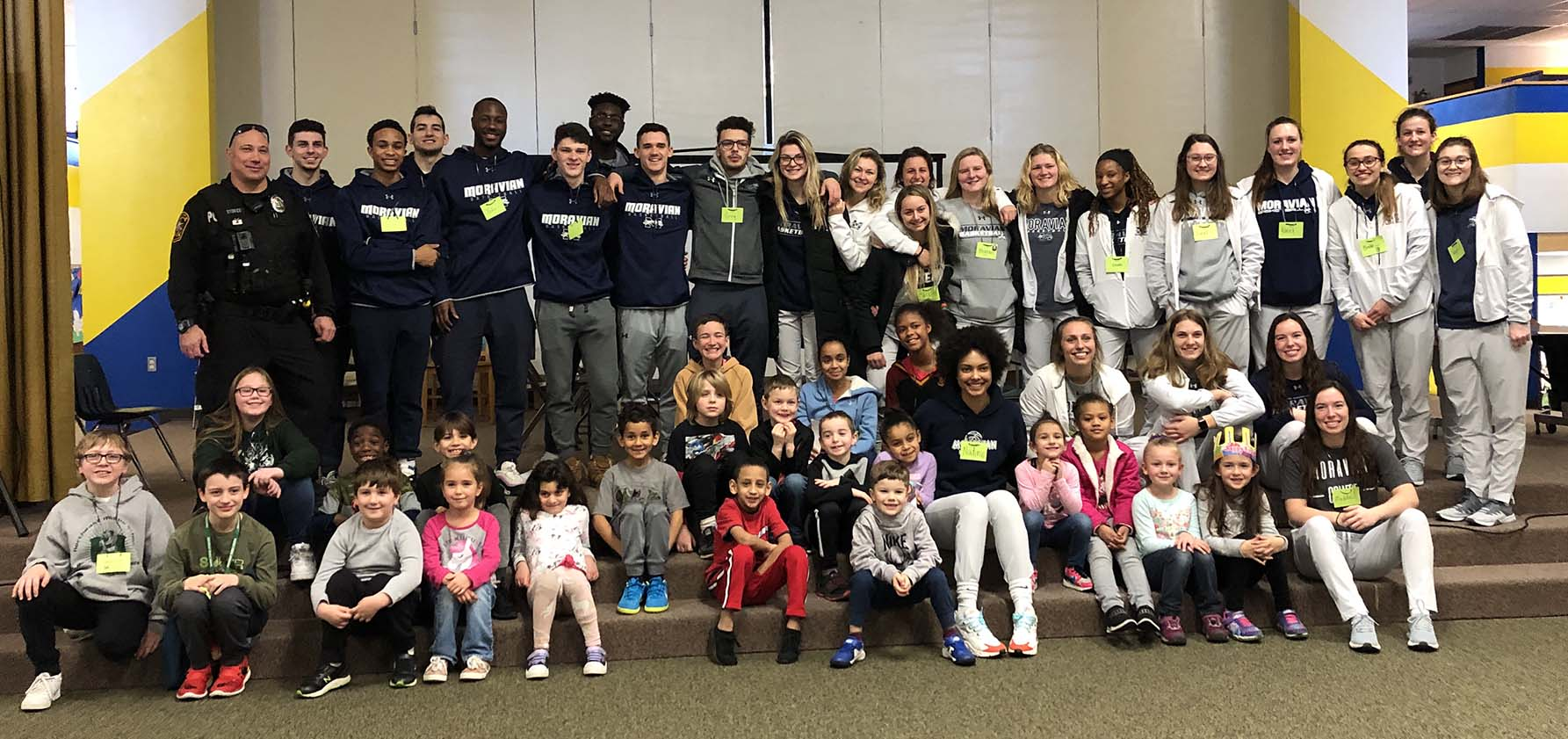 Moravian College basketball players gather with children from William Penn Elementary for a photo op.