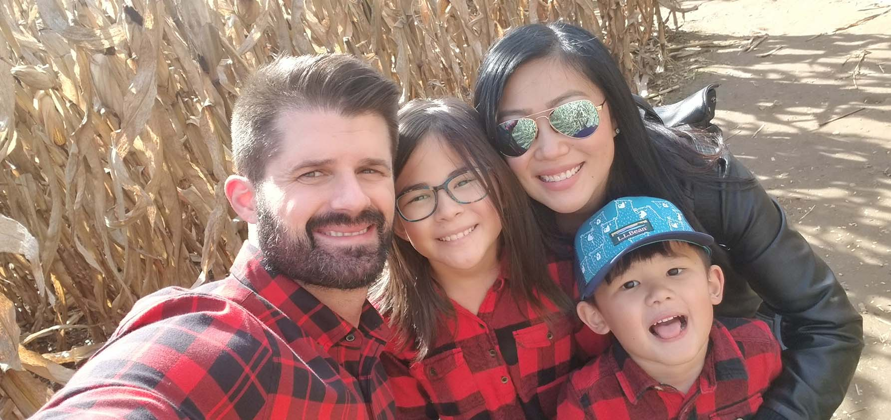 Jessica Weaver with her husband, daughter, and son having fun at a cornfield in fall.