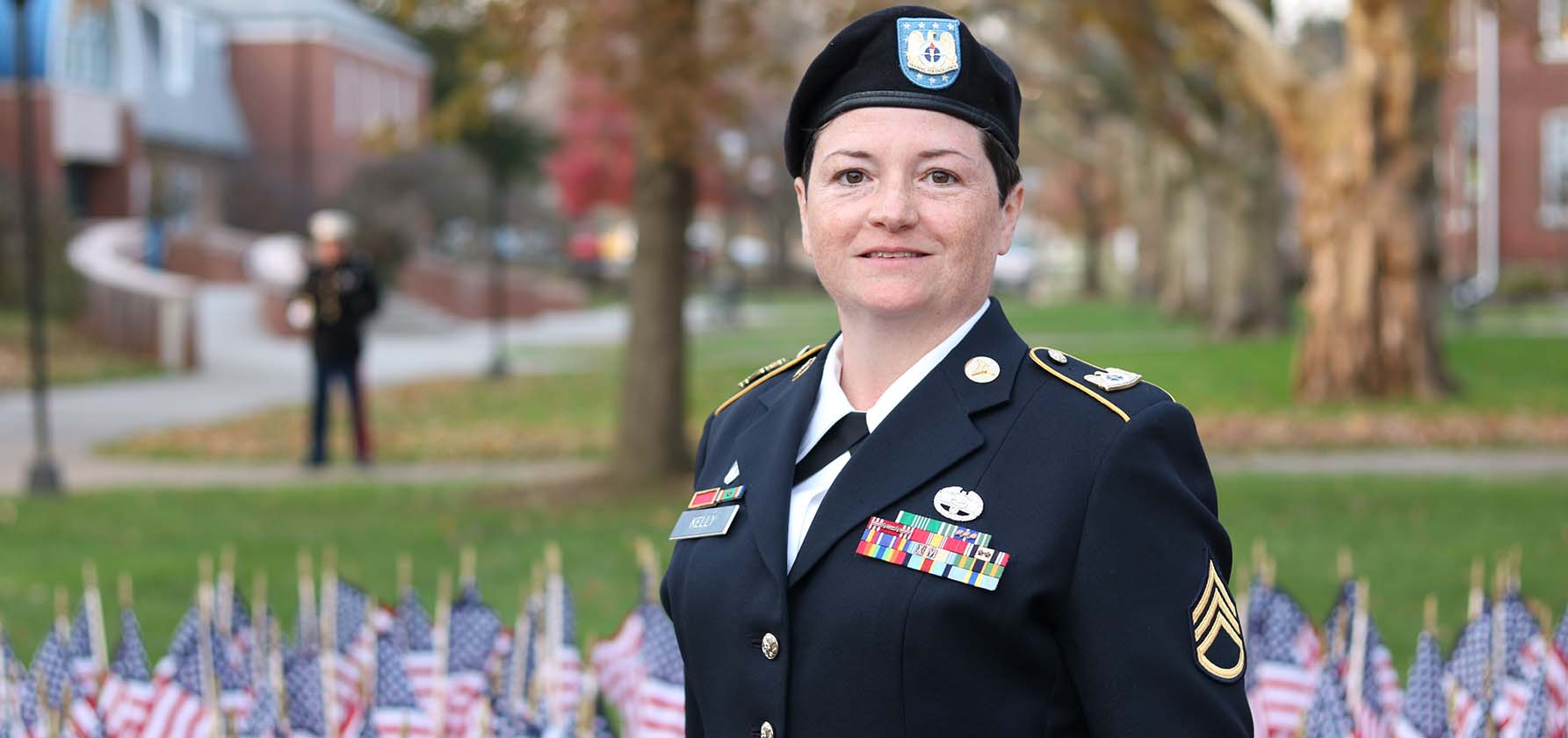Marilyn Kelly-Cavotta, director of veteran and military affairs stands in uniform in front of American flags placed in the ground on Moravian's Campus for Veterans Day.