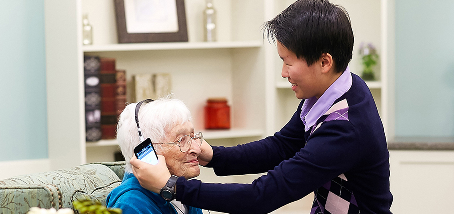 Maggie helps an elderly woman put on headphones
