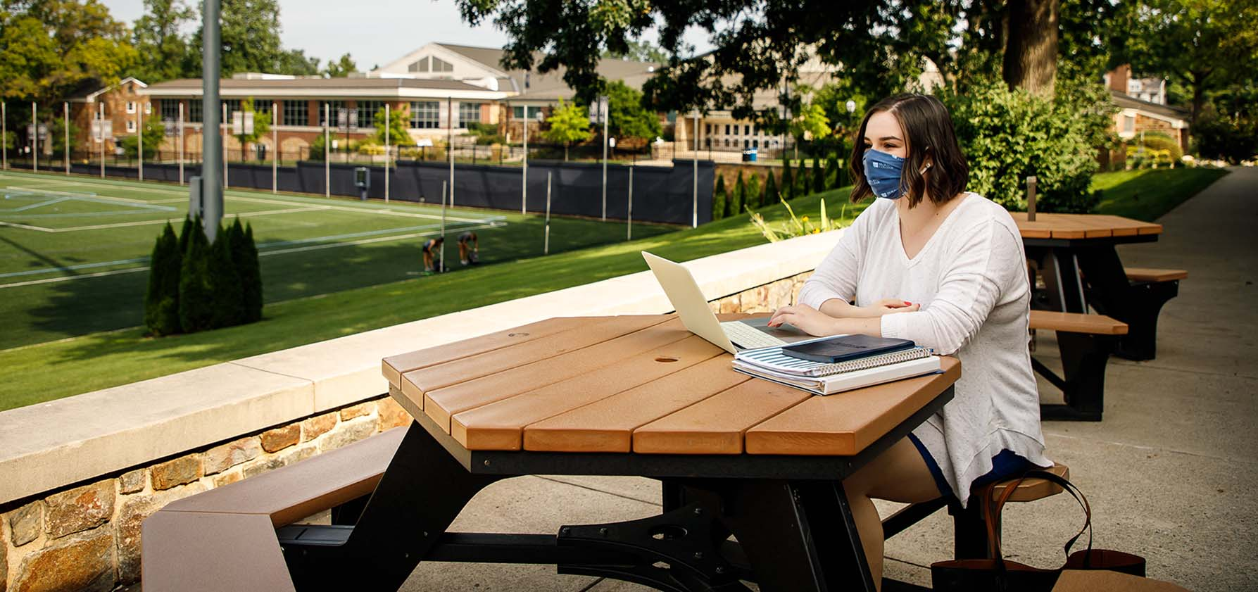 A Moravian College student with her MacBook sits at a picnic table outside the HUB as she Zooms in to her online course.