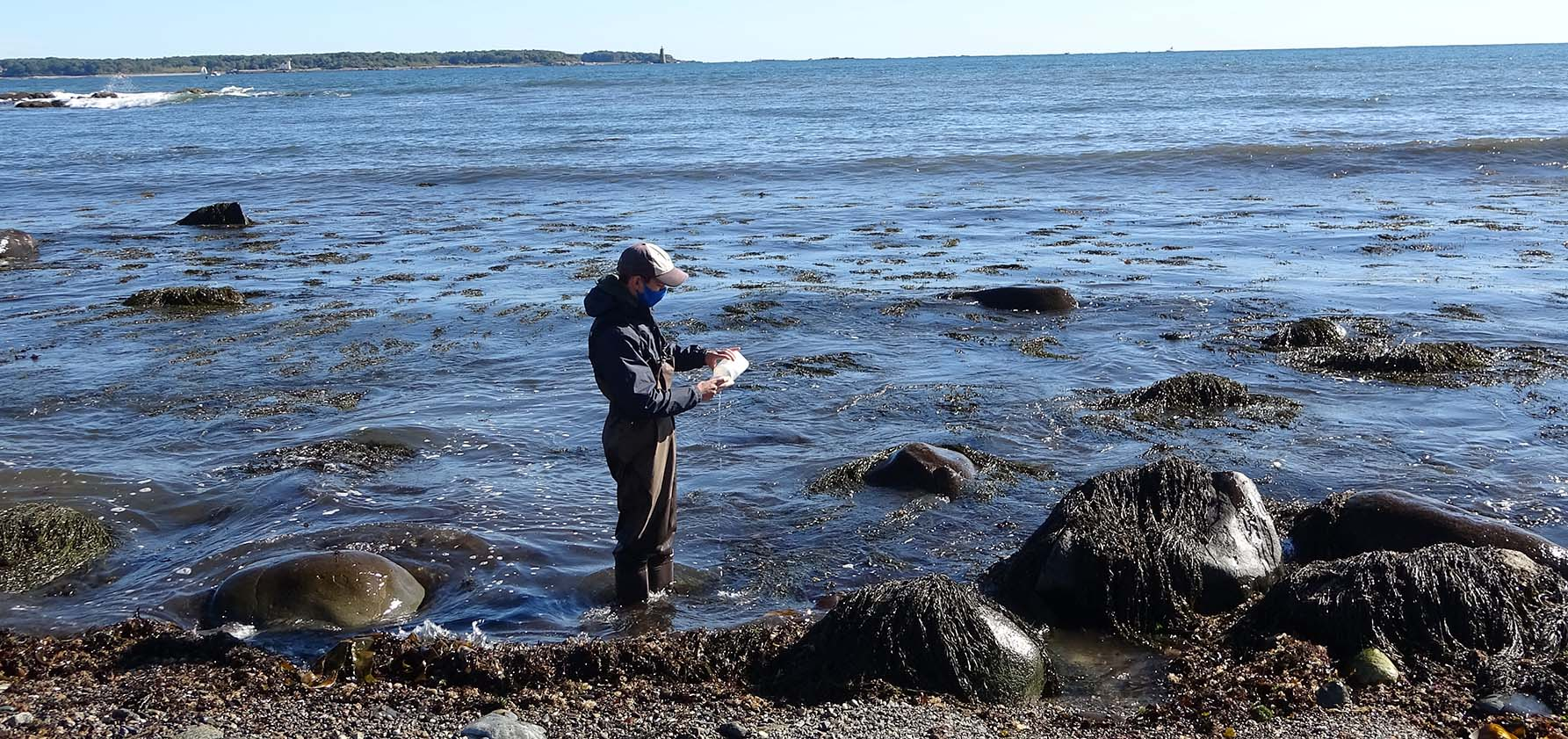 A Moravian College student-researcher takes a water sample along Oregon's rocky coastline.