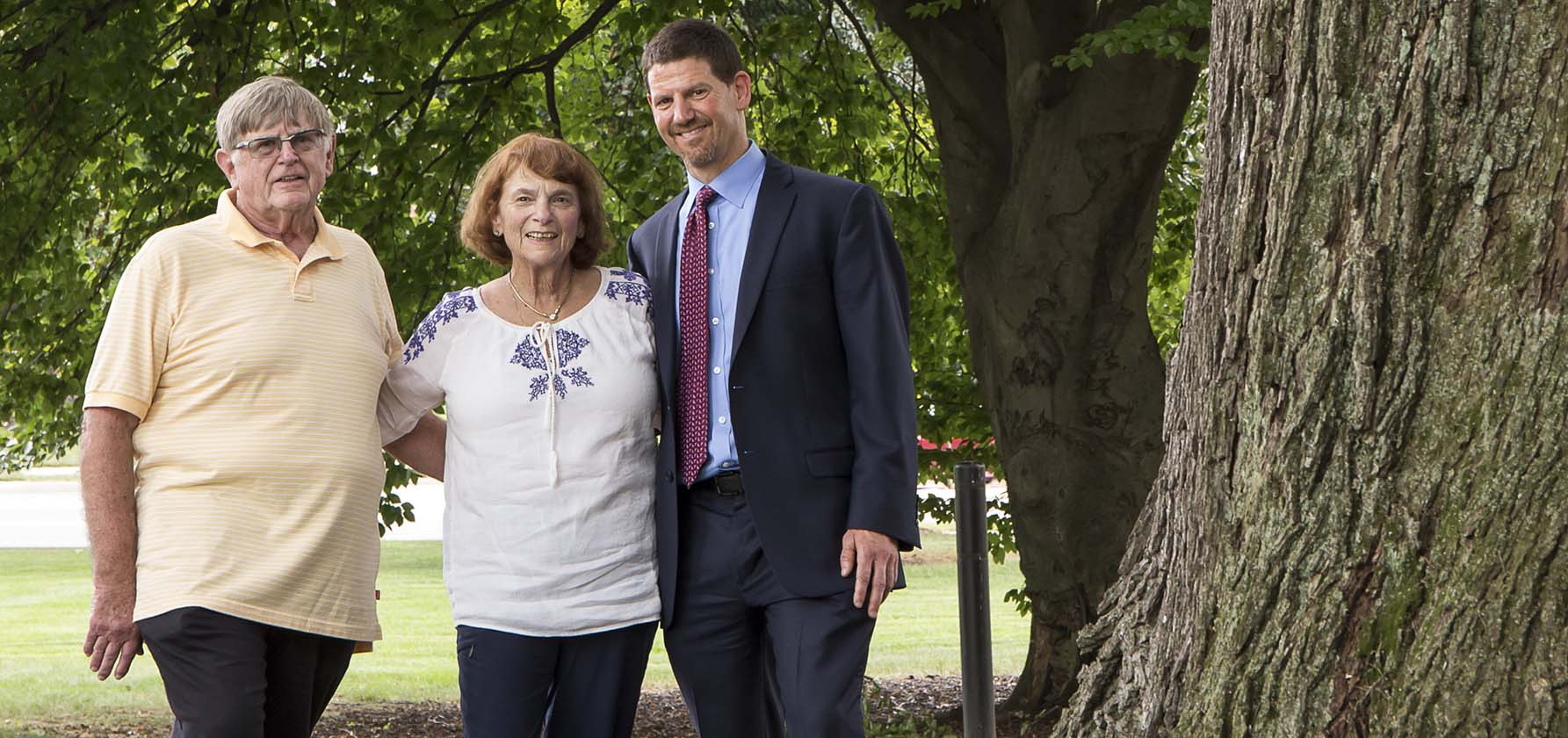 Jon Soden '91 (right) stands among the trees on Moravian's campus with his mother (center) and father (left).