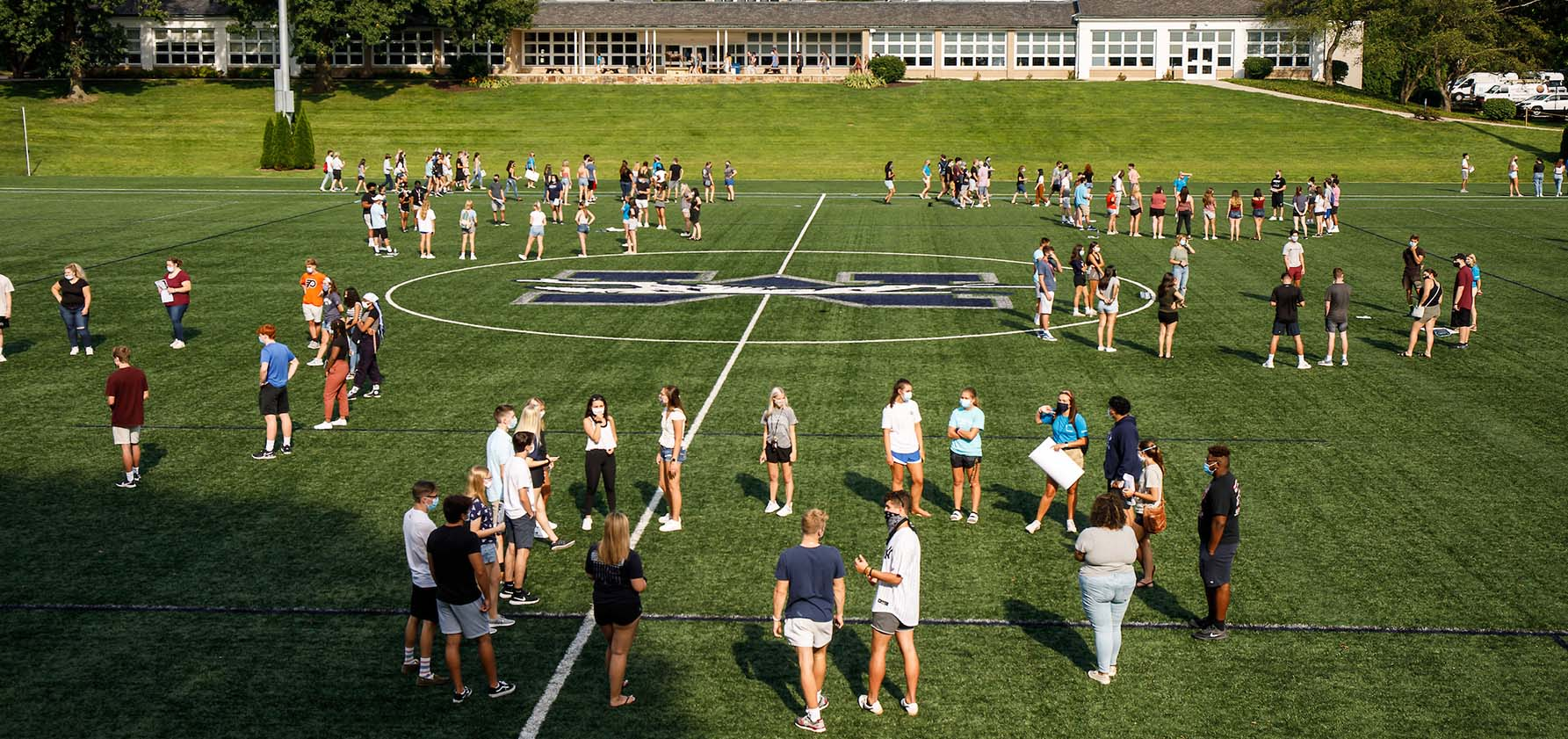 Students participate in orientation activities in small physically distanced groups on Makuvek Field.